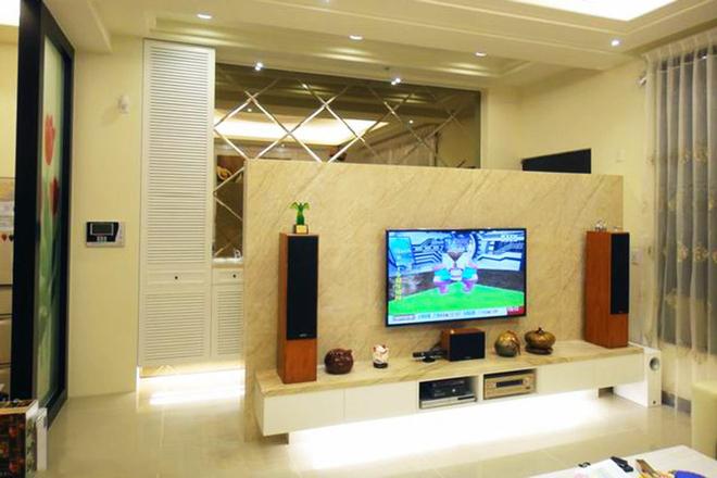 沙发背墙以古典,对称的线板展现空间质韵,电视墙则使用仿石材磁砖,不