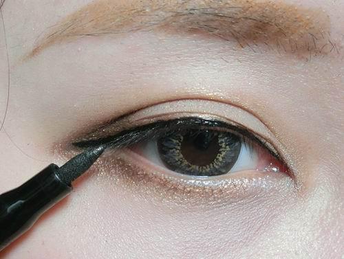 再用眼线液笔化一条细眼线,在眼角眼尾也描画上